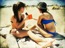 Two girls in the beach with texture. Young beautiful women taking photos on beach with cellphone camera Stock Photography