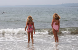 Two girls at the beach. Two young girls watching a person swim by on a Maine beach Stock Images