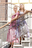 Two girls in beautiful dresses on the stairs. Shooting outdoors Stock Photos