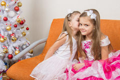 Two girls in beautiful dresses whispering sitting on couch. At Christmas tree Royalty Free Stock Photo