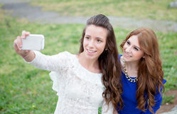 Two girls by becoming a photo with the phone in the park Royalty Free Stock Images