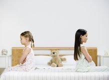Two girls on bed. Two girls, arms folded, back to back Stock Photos