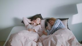 Two girls in the bed are waking up in the morning light. Two girl friends or a homosexual couple are lazily waking up in the morning in their big and comfy bed stock footage