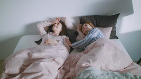 Two girls in the bed are waking up in the morning light. Two pretty caucassian girls friends or a homosexual couple are waking up in the bed in the morning stock footage