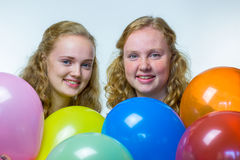 Two girls behind various colored balloons Royalty Free Stock Image