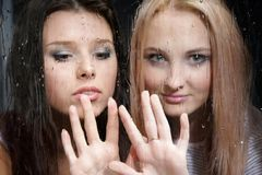 Two girls behind wet window Stock Images