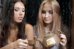 Two girls behind wet window Royalty Free Stock Photos