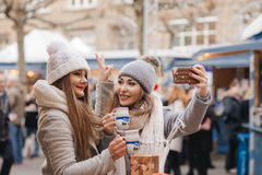 Two girls best friends  drink hot wine and make a self photo on Royalty Free Stock Images