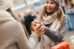 Two girls best friends giving presents on christmas market Stock Image