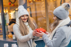 Two girls best friends giving presents on christmas market Royalty Free Stock Photography