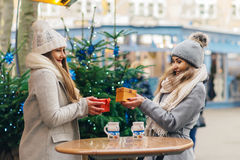 Two girls best friends giving presents on christmas market Stock Images