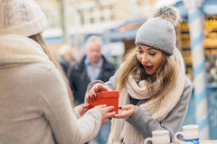 Two girls best friends giving presents on christmas market Royalty Free Stock Image
