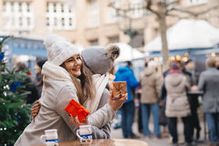 Two girls best friends giving presents on christmas market Royalty Free Stock Photo
