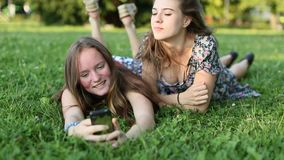 Two girls best friends lying on the green grass and fun take a selfie on smartphone. Two young girls best friends lying on the green grass and fun take a selfie stock video footage