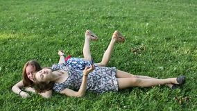 Two girls best friends lying on the green grass and fun take a selfie on smartphone. Two young girls best friends lying on the green grass and fun take a selfie stock video