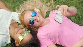 Two girls best friends lying on lawn, taking photos on cellphone, fun in park