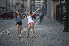 Two girls best girlfriends fooling around in evening old town. Royalty Free Stock Images