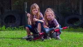 Two girls on a bicycle repair solar green glade. Young mechanic at work. Girl repairs a bike on a sunny green glade stock video footage