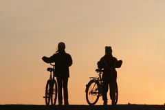 Two girls on bicycles. A sunset (sunrise Stock Image