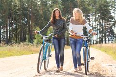 Two girls with bicycles in countryside Stock Image
