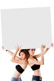 Two girls with a big sign. Two girls holding up a big sign Stock Image