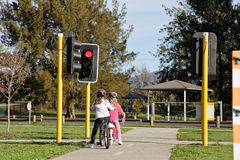 Two girls on bikes at stop light. Two girls on bikes waiting at a red light traffic control Royalty Free Stock Images