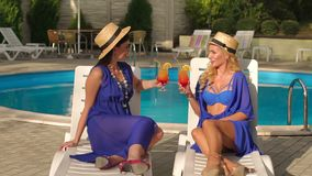 Two girls in bikini drinking cocktails by pool. Two beautiful sexy girls in bikini and silk dresses sitting on the sun loungers by the pool and clink glasses stock video footage