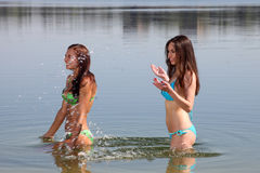 Two girls in bikini play in a water Stock Photo