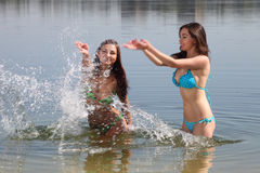 Two girls in bikini play in a water Stock Image