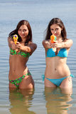 Two girls in bikini play with a water guns royalty free stock photo
