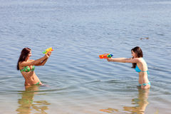 Two girls in bikini play with a water guns Royalty Free Stock Image