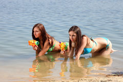 Two girls in bikini play with a water guns stock photo