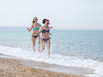 Two girls in bikini running along seashore splashing sea water Stock Photo