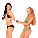 Two girls in bikinis. Playing. White background Royalty Free Stock Photography