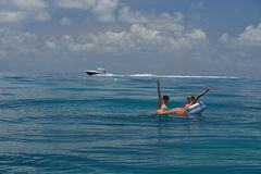 Two girls in bikinis on floating device at open waters. Of Caribbean with boat on background Stock Photo