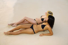 Two girls in bikinis on a sandy beach Stock Photo