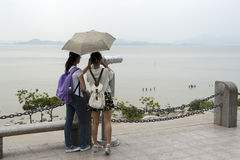 Two girls with binoculars looking at Hong Kong. Royalty Free Stock Images