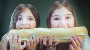 Two girls biting a big baguette royalty free stock image