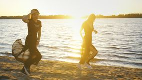 Two girls in a black dress walk along the beach and dance. Two young women walking along a beach on summer day. Best friends on a beach vacation stock video footage