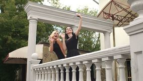 Two girls in black evening dresses take a selfie. Two sexy girls in black long evening dresses take a selfie standing on a beautiful old balcony stock footage