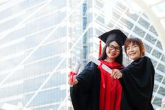 SHOW SUCCESS IN EDUCATION. Two girls in black gowns and hold diploma certificate with happy graduated stock photography