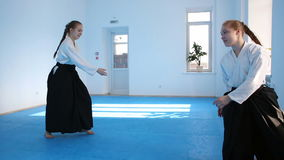 Two girls in black hakama practice Aikido. On martial arts training stock footage