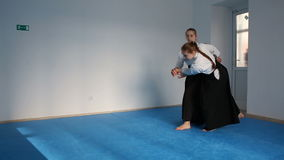 Two girls in black hakama practice Aikido. On martial arts training stock video footage