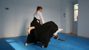 Two girls in black hakama practice Aikido. On martial arts training stock video