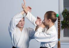 Two girls in black hakama practice Aikido Stock Photos