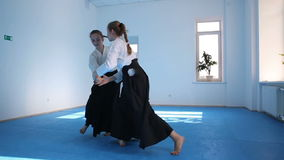 Two girls in black hakama practice Aikido. On martial arts training. Slow motion stock video footage