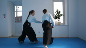 Two girls in black hakama practice Aikido. On martial arts training. Slow motion stock footage