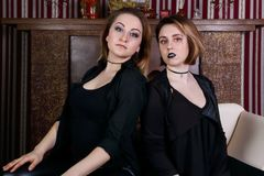 Two girls in black pose on ottoman. In studio with decorative fireplace Royalty Free Stock Photography