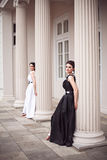 Two girls in black and white long dresses Stock Images