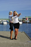Two girls blonde stand on the pier. And point a finger stock images